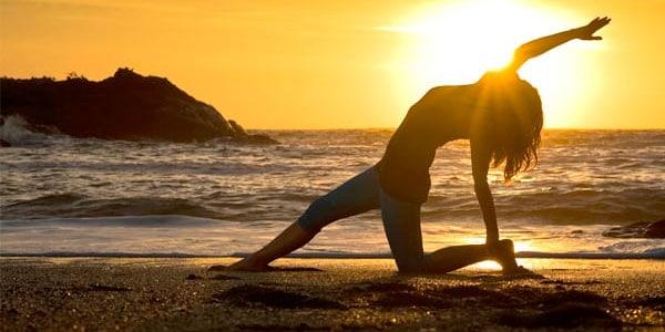 Mujer en la playa haciendo yoga